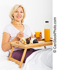 pensioner with orange juice, berries and yogurt
