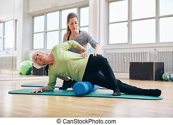 Instructor helping senior woman for a myofascial release...