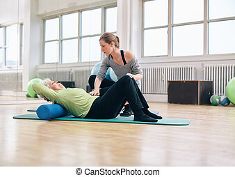 Physical therapist helping elder woman at gym - Senior woman...