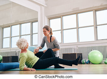 Female trainer helping old woman getting up at gym - Female...