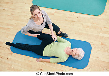 physical therapist helping senior woman do leg stretches