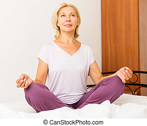 Mature woman doing yoga in bed at bedroom