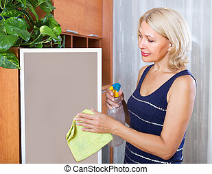 Mature girl cleaning glass door of furniture