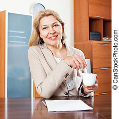 smiling  woman sitting at a table in the office