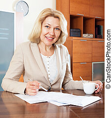 mature woman working with documents at table in office...