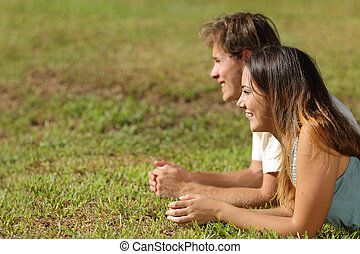 Couple lying on the grass and looking away
