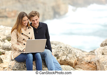 Couple sharing a laptop on the beach on holidays - Couple...