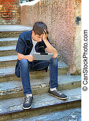 Sad Teenager with Tablet Computer on the landing steps of...