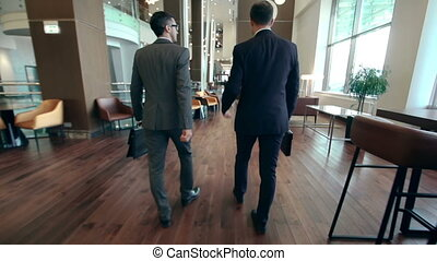Business Ways - Camera following two businessmen walking...
