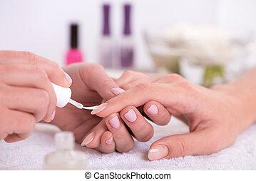 client and manicurist in manicure salon - manicurist doing...