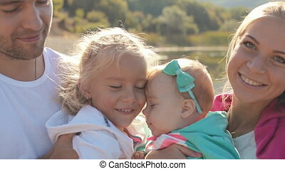 Caring parents kiss their amazing daughters