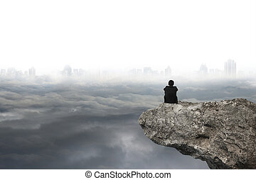 man sitting on cliff with gray cloudy sky cityscape...