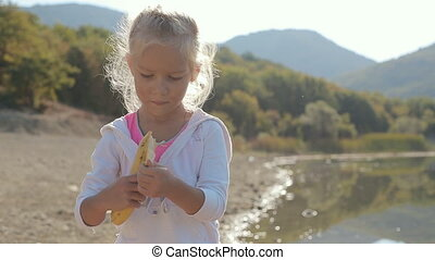Little beautiful girl stands near a lake, cleans banana and starts eating it
