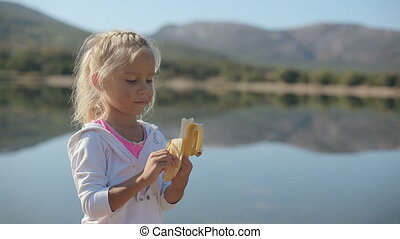 Cute little girl eating a banana while standing next to  an incredibly beautiful lake