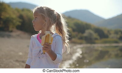 Amazing little girl eating a banana near the lake next to...