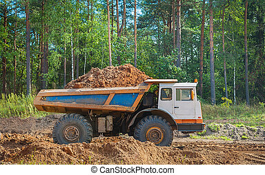 old tipper vith clay ground standing in forest