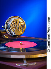 Old gramophone on blue background very close up