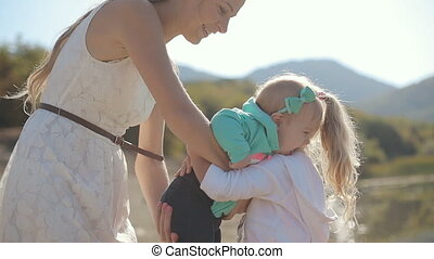 Beautiful mom in sundress gives her baby in arms of eldest...
