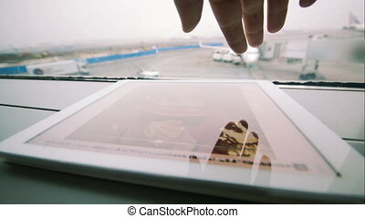 Looking through the photos on tablet PC at airport -...
