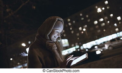 Woman with touch pad typing on her way in night city -...