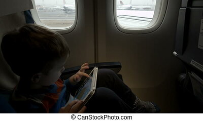 Boy sitting in the plane and using tablet PC - Little boy...