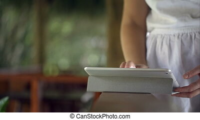 Woman using tablet computer on handrail - Close-up shot of a...