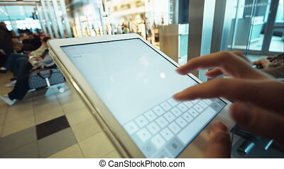 Woman using tablet PC in waiting room of airport or station...