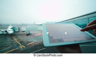 Using tablet computer by the window at airport - Close-up...