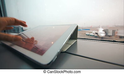 Typing on tablet computer on windowsill at airport -...