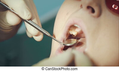 Dentist providing examination of a woman - Macro shot of...