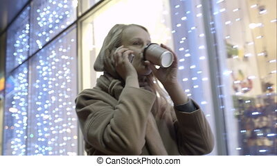 Woman talking on phone and drinking coffee while walking in street