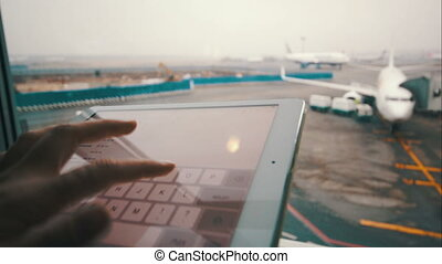 Using touch pad by the window at airport - Close-up shot of...
