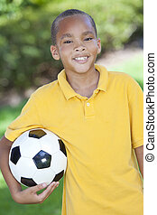 African American Boy Child Playing With Football or Soccer...