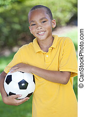African American Boy Playing With Football or Soccer Ball -...
