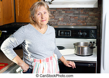 Friendly grandmother cooking - Friendly smiling grandmother...