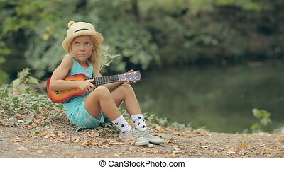 Little blond girl in a straw hat sitting near the river and playing guitar
