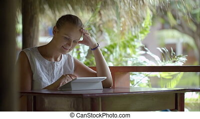 Woman using tablet PC sitting outdoor in tropics