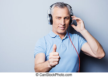 Listening to good music helps you at any situation. Portrait of senior man in headphones listening to music and showing his thumb up while standing against grey background
