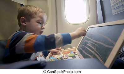 Boy in the plane drawing on board with chalk - Little boy in...