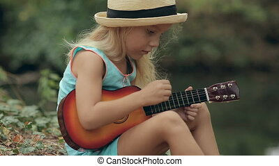 Little girl in a straw hat sitting in the forest near the river and playing guitar