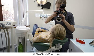 Dentist making shots of womans smile after treatment -...
