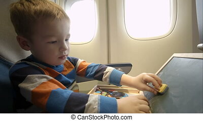 Little boy in the plane with wooden box
