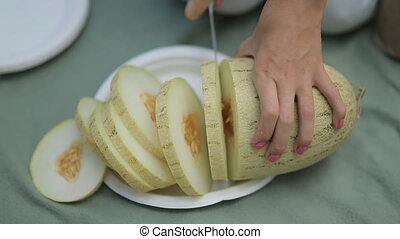 The girl with a knife cuts ripe juicy melon - Close up of...