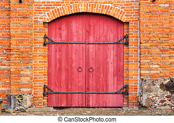 old wooden gate in a red brick wall