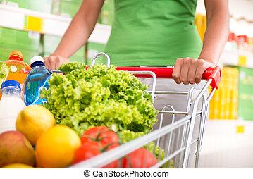 Full shopping cart - Woman in green t-shirt pushing a...