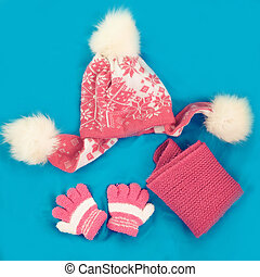Childrens cap, scarf and gloves on a blue background
