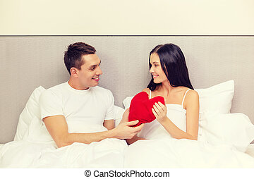 smiling couple in bed with red heart shape pillow - hotel,...