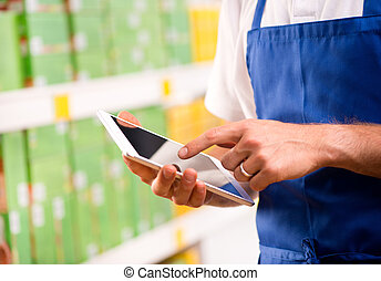 Sales clerk using tablet - Sales clerk wearing apron using a...