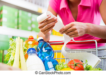 Expensive grocery bills - Unrecognizable woman checking a...