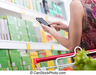 Woman with mobile at supermarket - Unrecognizable woman at...